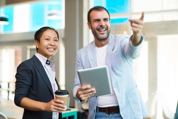 Positieve latijnse en aziatische managers die koffiepauze in bureau hebben