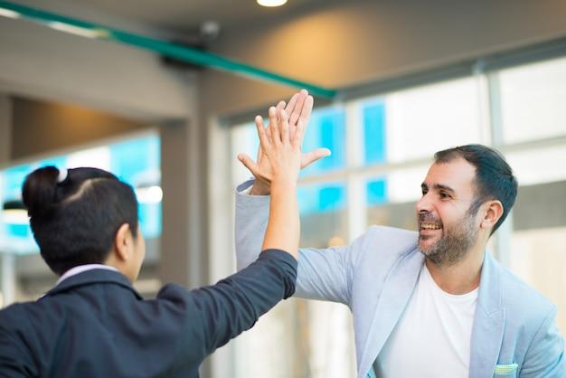 Positieve latijnse en aziatische managers hoog fiving