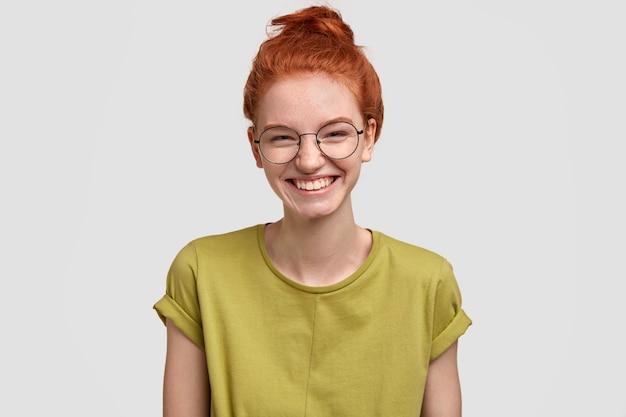 Positieve leerling met sproeten heeft rood haar, lacht breed, draagt een ronde optische bril en een groen t-shirt, staat tegen een witte muur, verheugt zich op goede momenten in het schoolleven, herinnert zich iets aangenaams
