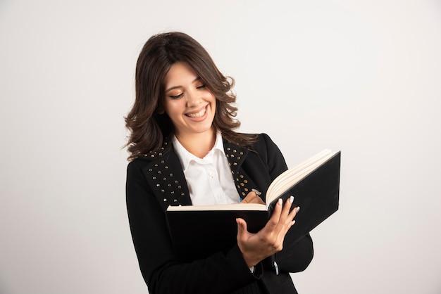 Positieve leraar die notities schrijft voor haar klas.