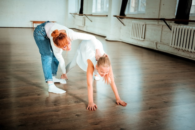 Positieve leraar. slanke mooie balletleraar met rood haar die mooi glimlacht tijdens het werken met haar student