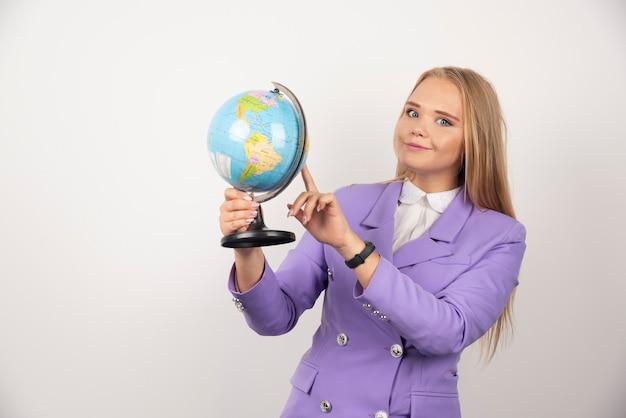 Positieve leraar wijzend op wereldbol op wit.