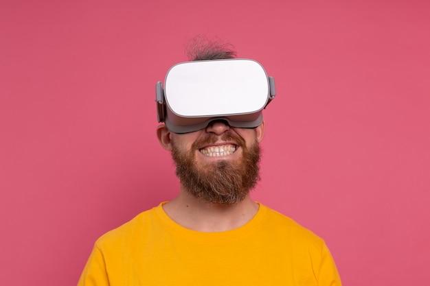 Positieve leuke gelukkige man in vr-bril op studio achtergrond