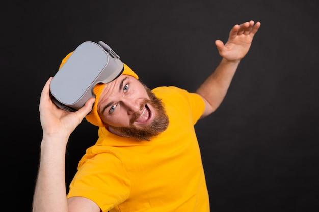 Positieve leuke gelukkige man in vr-bril op studio achtergrond Gratis Foto