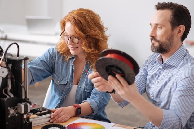 Positieve leuke professionele ontwerper die samen zit en in team werkt tijdens het ontwikkelen van 3d-ontwerpen