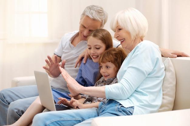 Positieve, levendige, geweldige kinderen die een videogesprek voeren en vertellen hoeveel plezier ze hebben met hun grootouders