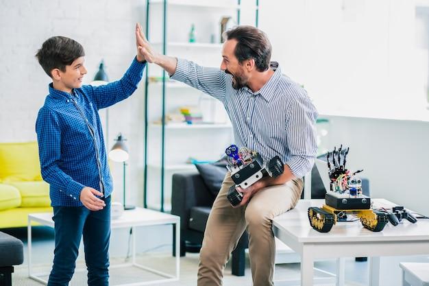 Positieve liefhebbende vader die zijn zoon high five geeft terwijl hij een robotapparaat vasthoudt