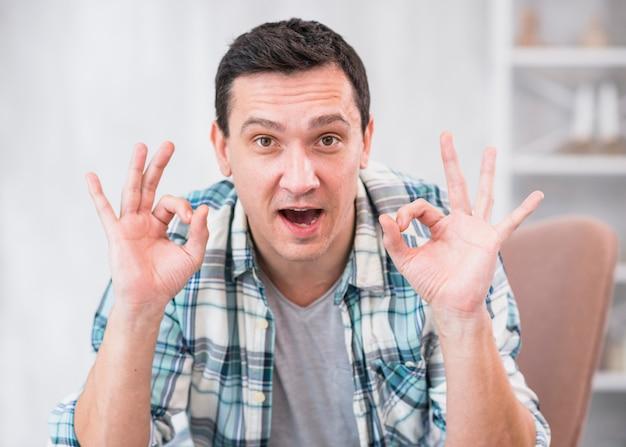 Positieve man die ok gebaar op stoel thuis toont