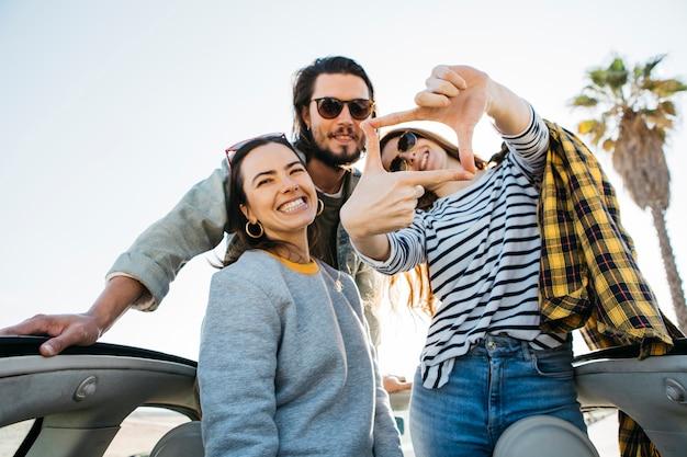 Positieve man en glimlachende vrouwen die frame maken, die pret hebben en uit auto leunen