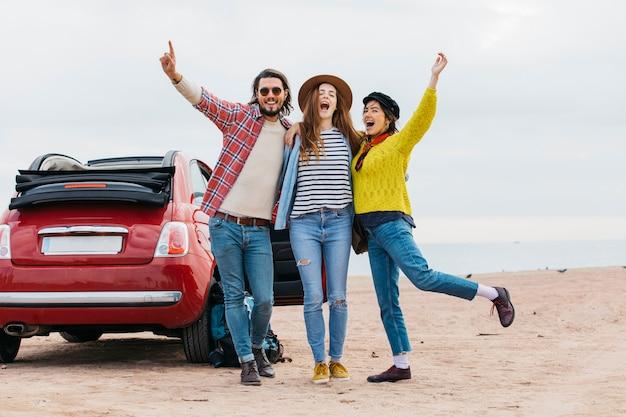 Positieve man en huilende vrouwen die dichtbij auto op overzeese kust omhelzen