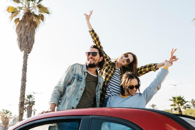 Positieve man en lachende vrouwen met plezier en leunend uit auto