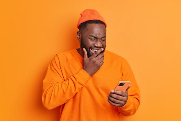 Positieve man giechelt positief geconcentreerd op het smartphonescherm kijkt naar grappige video op internet of lacht om ontvangen bericht gekleed in lichte casual kleding geïsoleerd op een oranje muur