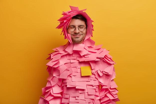 Positieve man heeft roze zelfklevende briefjes geplakt rond lichaam en hoofd, maakt creatief papieren kostuum van stickers, draagt een bril, werkt op kantoor, geïsoleerd over gele muur, houdt de ogen dicht