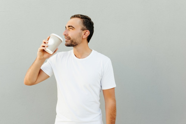 Positieve man houdt papieren kopje koffie geïsoleerd over grijze muur