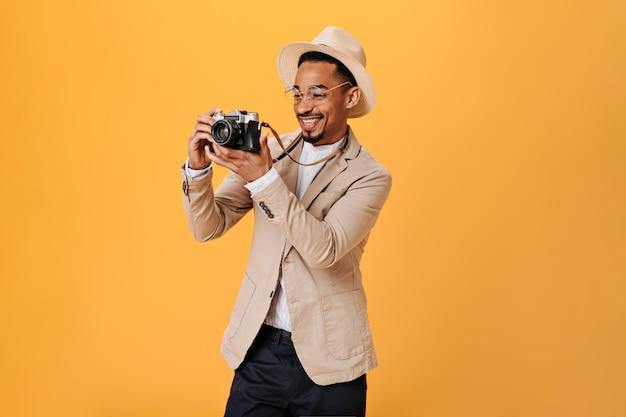 Positieve man in bril en hoed houdt retro camera vast en lacht op oranje muur