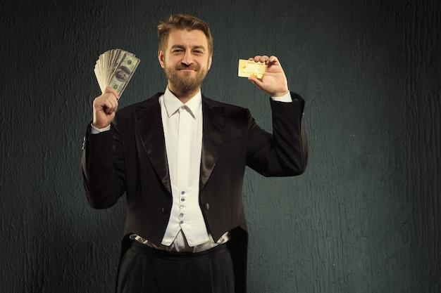 Positieve man in een slipjas biedt een creditcard en geld aan.