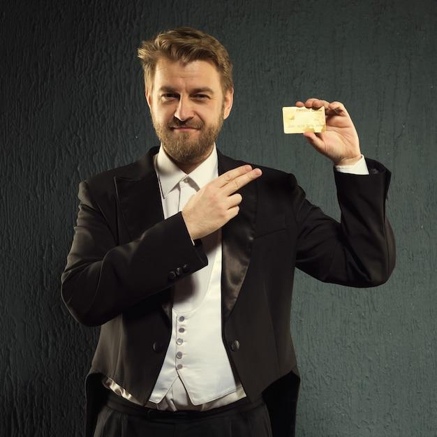 Positieve man in een slipjas wijzende vinger naar de creditcard.