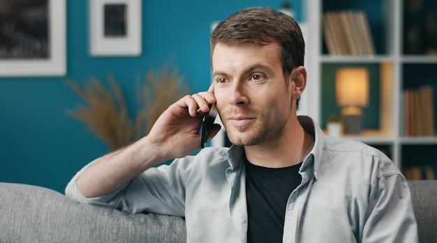 Positieve man in vrijetijdskleding praten over mobiel zittend op de bank in appartement, shot van de borst