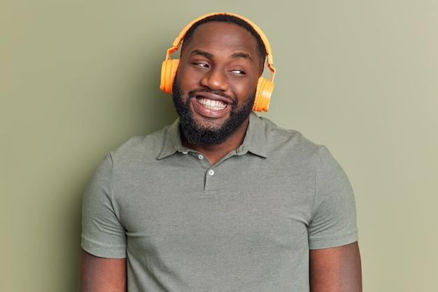 Positieve man met brede glimlach luistert naar favoriete audiotrack via koptelefoon kijkt weg en kijkt bedachtzaam gekleed in casual t-shirt poseert tegen donkergroene muur