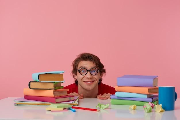 Positieve man met bril draagt in rood t-shirt, verstopt aan de tafel met boeken, kijkt naar de camera en glimlachen, geïsoleerd op roze achtergrond.