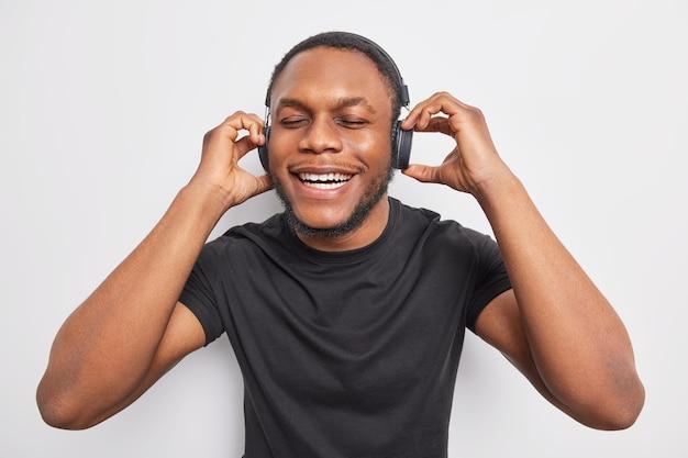 Positieve man met donkere huid en baard geniet van perfect geluid in stereokoptelefoon houdt ogen dicht glimlacht breed