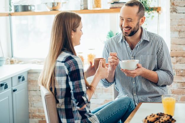 Positieve man met een kom lachend aan tafel en een vrouw met een kopje glimlachend