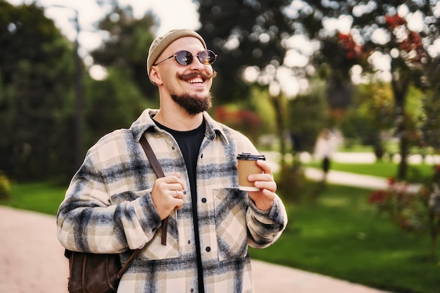 Positieve man met hoed en zonnebril houdt koffie vast terwijl hij met rugzak in stedelijke omgeving wandelt