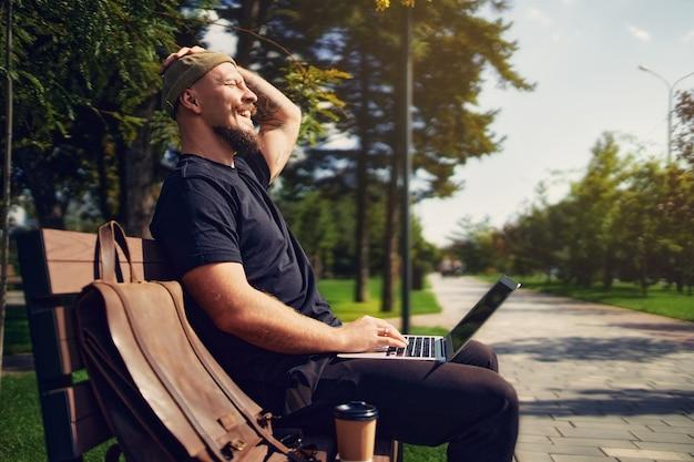 Positieve man met laptop die buiten op afstand werkt terwijl hij op een bankje zit in het stadspark op afstand