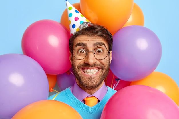 Positieve man omringd door partij ballonnen poseren