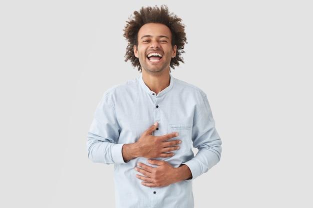 Positieve man raakt buik, kan niet stoppen met lachen, in een goed humeur