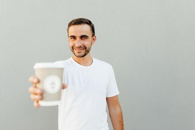 Positieve man wees papieren kopje koffie geïsoleerd over grijze muur
