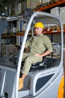 Positieve mannelijke magazijnmedewerker in overall en veiligheidshelm heftruck rijden, stuurwiel vasthouden