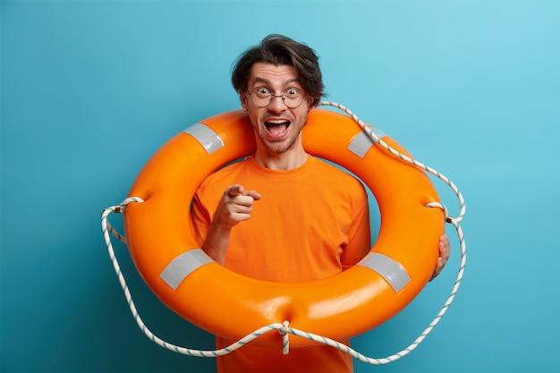 Positieve mannelijke toerist poseert met opgeblazen zwemring leert om punten direct bij de camera te zwemmen