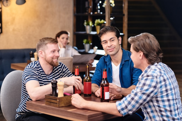 Positieve mannelijke vrienden die van vrije tijd in bar genieten