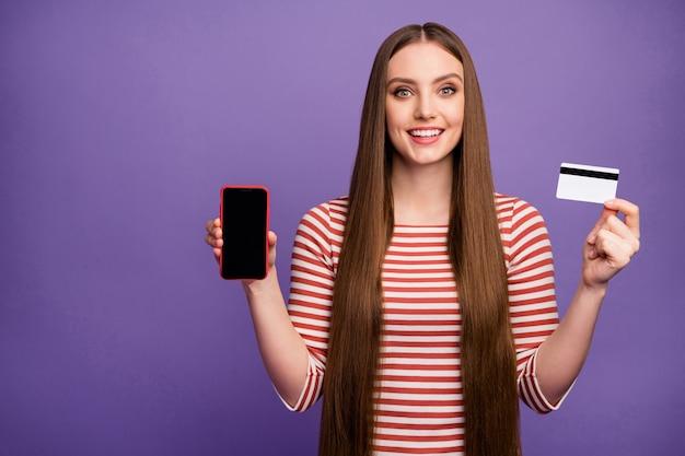 Positieve meisje hipster houdt smartphone creditcard aanwezig moderne technologie promotie ze betaalt gemakkelijk bank betalingsdienst draag gestreepte witte trui trui geïsoleerde paarse kleur muur