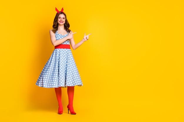 Positieve meisje wijs wijsvinger kopie ruimte gele achtergrond