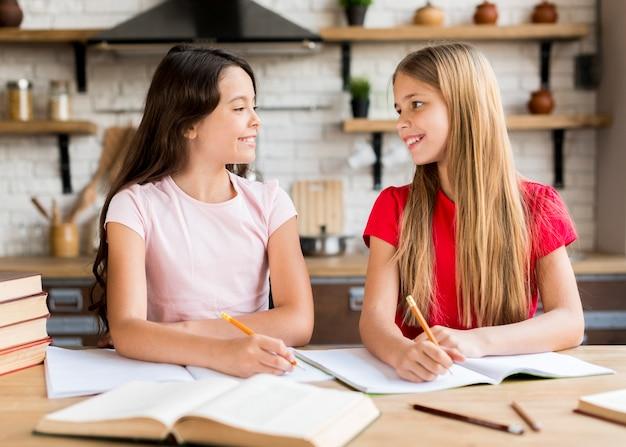 Positieve meisjes die in voorbeeldenboeken samen schrijven