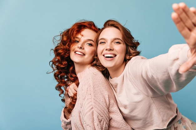 Positieve meisjes die plafully op blauwe achtergrond stellen. studio die van vrienden is ontsproten die pret hebben.