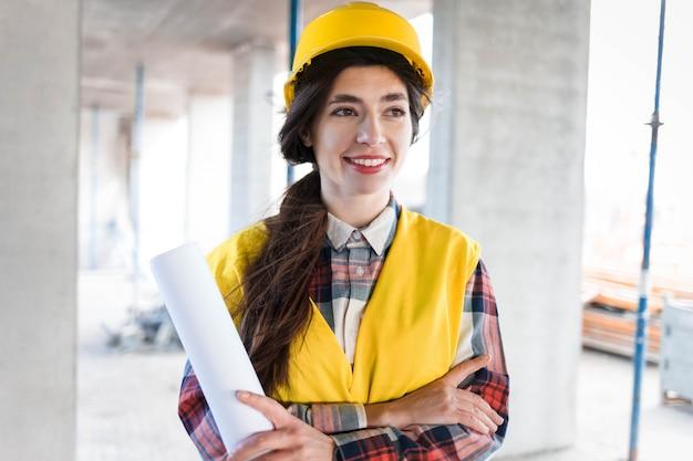 Positieve meisjesingenieur bij bouwwerf met in hand tekeningen ive glimlach de ingenieursbouwer van de glimlachvrouw bij een bouwwerfholding document met tekeningen