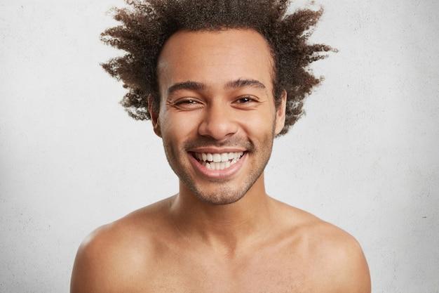 Positieve menselijke emoties concept. knappe jongeman lacht graag, toont perfecte witte tanden