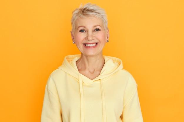 Positieve menselijke emoties en reacties. portret van zorgeloze gelukkig senior vrouw met geverfd stijlvol kort haar camera kijken met brede vrolijke glimlach, hoodie dragen, actieve levensstijl kiezen
