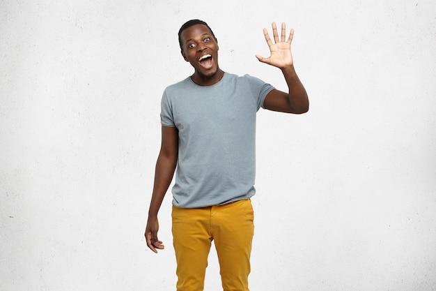 Positieve menselijke emoties, gezichtsuitdrukkingen, gevoelens, houding en reactie. vriendelijk ogende beleefde jonge afro-amerikaanse man gekleed in grijs t-shirt en mosterdjeans die hallo zegt en met zijn hand zwaait