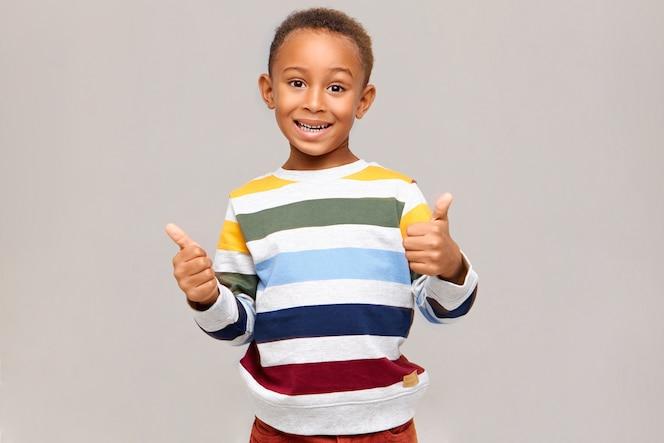 Positieve menselijke emoties, reacties en gevoelens. emotionele gelukkige donkere jongen in multi gekleurde trui duimschroef opwaarts gebaar maken, instemming, goedkeuring uiten, zijn like geven, breed glimlachen