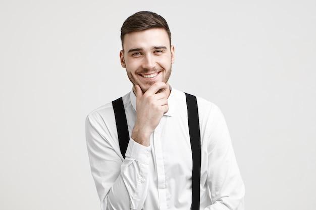 Positieve menselijke gezichtsuitdrukking, emoties, gevoelens en levensperceptie. vrolijke knappe jonge bebaarde man gekleed in een stijlvol wit overhemd met bretels, lachen om grap, wrijven over zijn stoppels