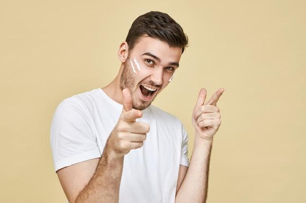 Positieve menselijke gezichtsuitdrukkingen, emoties en lichaamstaal. portret van knappe dolgelukkige jonge ongeschoren man met schuim op zijn wangen, opgewonden uitroepend en wijzende vingers