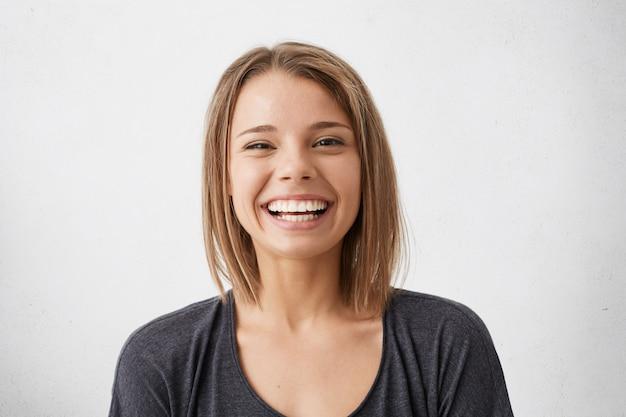 Positieve menselijke gezichtsuitdrukkingen en emoties. vrolijke aantrekkelijke tienermeisje met bob kapsel breed grijnzend, haar perfecte witte tanden laten zien terwijl ze leuke tijd binnenshuis doorbrengt