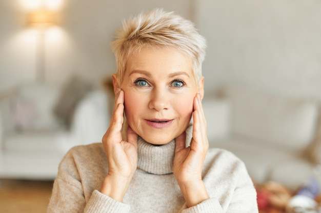 Positieve menselijke gezichtsuitdrukkingen, gevoelens, emoties en reacties. foto van emotionele aantrekkelijke rijpe vrouw met blond haar en blauwe ogen hand in hand op het gezicht, versteld staan van iets