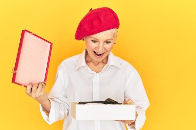 Positieve menselijke reacties en emoties. trendy emotionele vrouw van middelbare leeftijd met een rode motorkap die opgewonden roept, dolblij met een verbaasde blik, doos opent met onverwacht geschenk, mond openhoudt