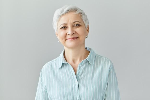 Positieve menselijke reacties, gevoelens en emoties. charmante elegante zestigjarige vrouw van middelbare leeftijd met kort grijs haar met een tevreden glimlach, haar ogen vol geluk en vreugde