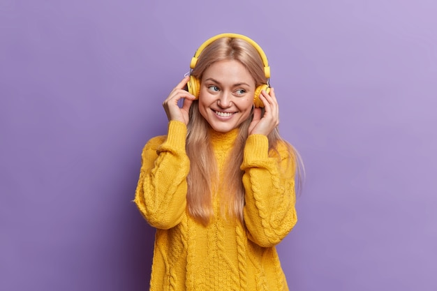 Positieve millennial meisje geniet van aangename muziek via koptelefoon in goed humeur glimlach gelukkig gekleed in gele trui